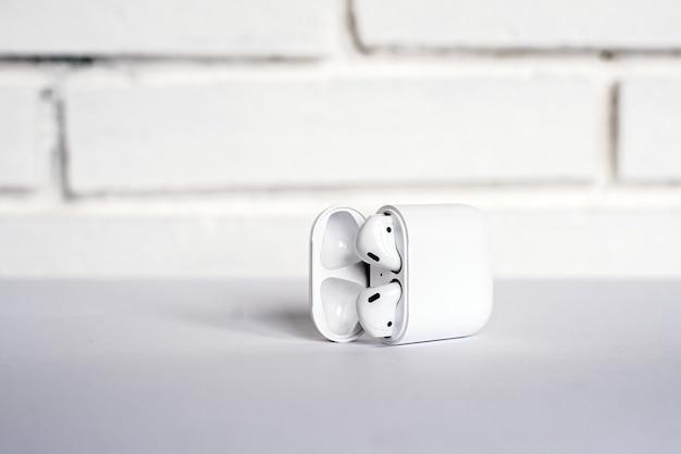 白いレンガの壁に対してテーブルに配置されたモダンな真のワイヤレスイヤフォンを備えたオープンボックス