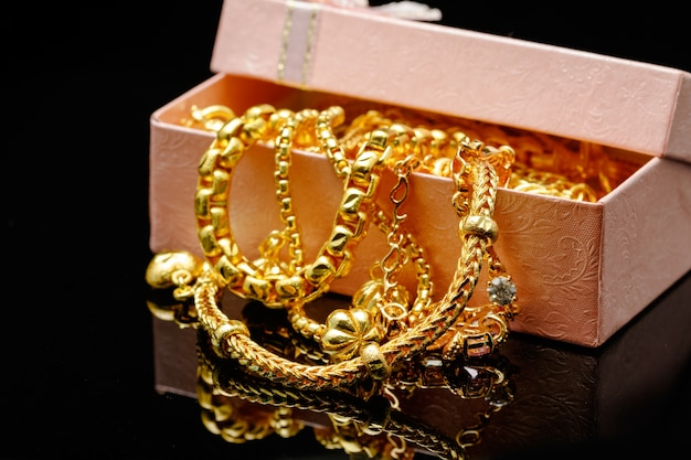 Open box with pile of various golden jewelry, isolated black background.