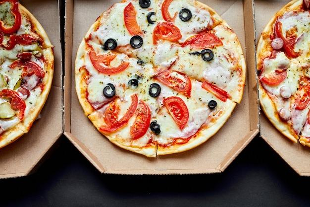 黒の背景に3つのピザをスライスしたホットでおいしいイタリアンの箱を開ける