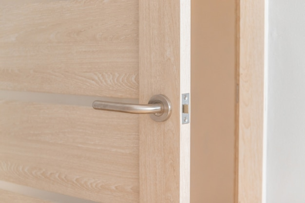 호텔이나 호스텔 룸에서 자물쇠와 금속 손잡이가있는 밝은 나무로되는 문 열기
