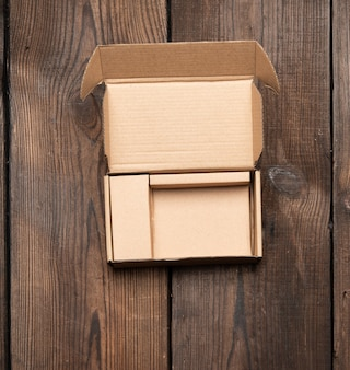Open brown cardboard paper box on wooden table, top view