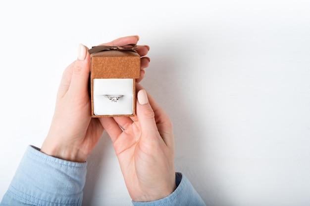 女性の手でリングと茶色の宝石箱を開きます。プレゼント。分離する