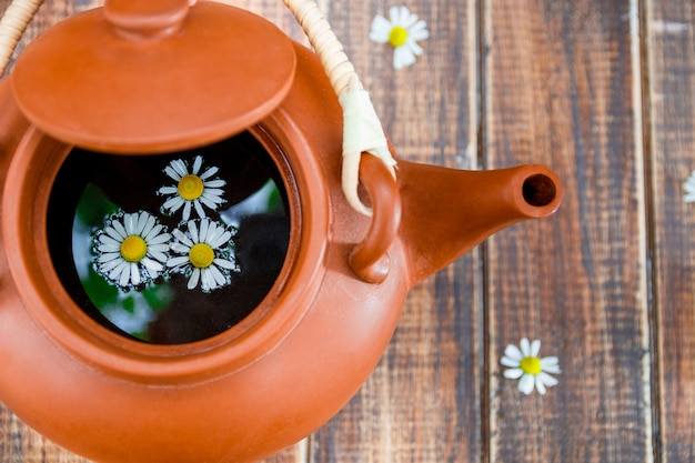 Open brown teapot with tea and flower of chamomile on wooden surface