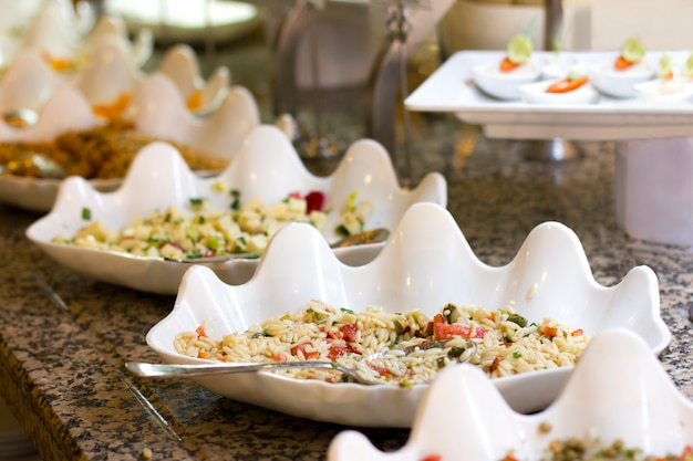 Open buffet at the hotel. rice salad and appetizers in white bowls