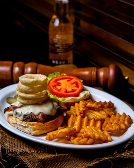 Open burger with meat, cheese sauce, onion rings and tomato with fried potatoes on a plate on a wooden table