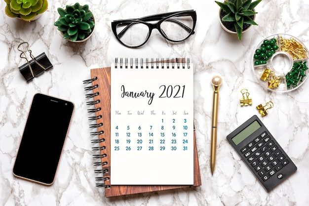 Open calendar january 2021, glasses, cup of coffee, pen, smartphone, succulents on marble table