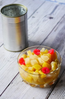 Open can of fruit cocktail on table