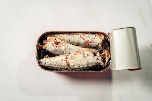 Open can of sardines in oil isolated on white simile marble surface.