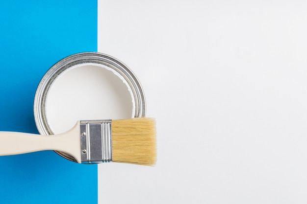 An open can of white paint and a brush on a blue and white