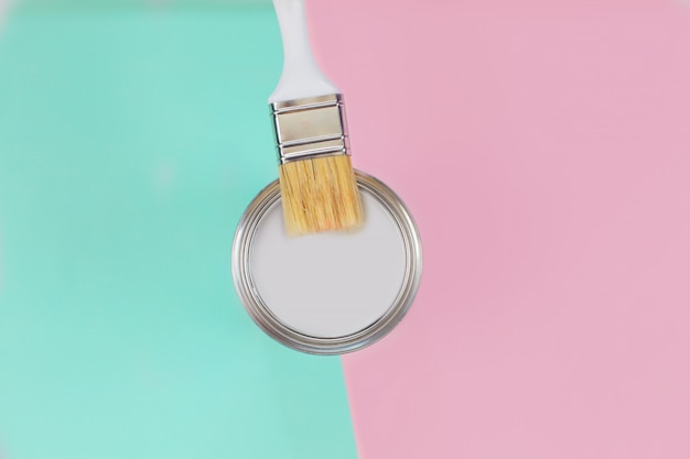 Open can with white paint and brush on mint and pink pastel background.