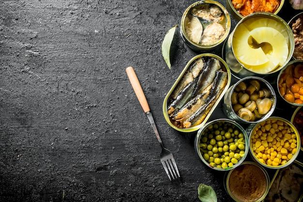 キノコ、パイナップル、トウモロコシ、魚の缶詰の缶を開けます。黒の素朴な表面に