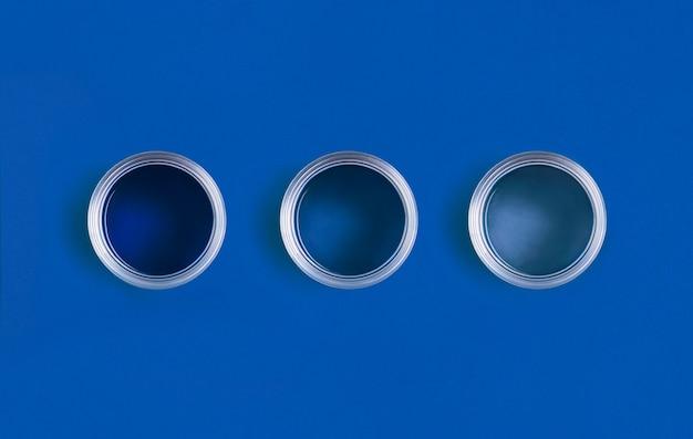 トレンディなクラシックブルーの背景に塗料の缶を開きます。 2020年の色。