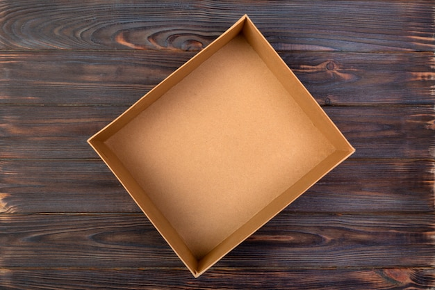 Open cardboard box on a dark table, wooden. top view