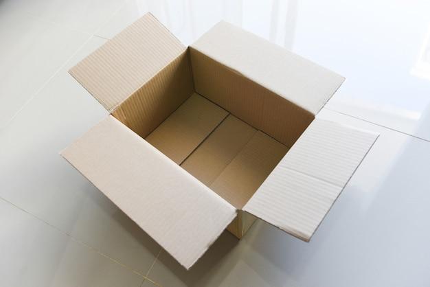 Открытая картонная коробка на полу