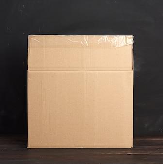開いた段ボール箱が茶色のテーブルの上に立って、商品の移動と梱包の概念
