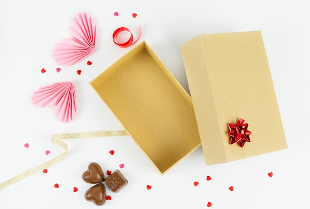 Open cardboard box with paper hearts and chocolates. valentine day, anniversary, mother's day and birthday greetings.