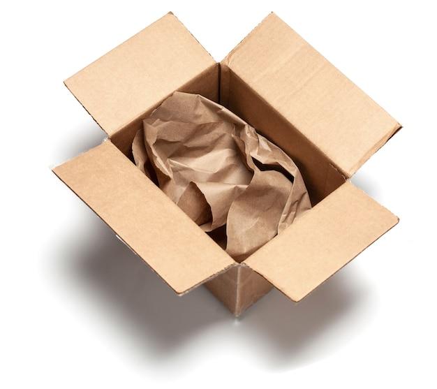 中に包装紙が入った段ボール箱を開けます。白い表面で隔離。上面図。