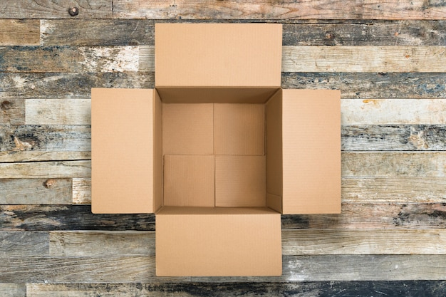 Open cardboard box on wooden background. corrugated carton box on vintage wooden texture. delivery concept. flat lay. top view