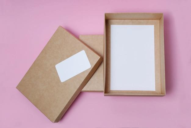 ピンクの背景の上面図にカバー付きの段ボールクラフトボックスを開きます。配信の概念