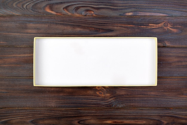 Open cardboard white box on a dark table, wooden background.