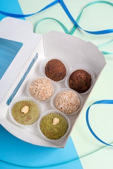 다채로운 파란색과 녹색 배경에 누워 다양한 채식 너트 트뤼플이있는 오픈 카톤 상자