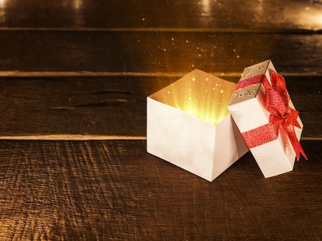 Open christmas white gift box with ray of magic light on wood desk.