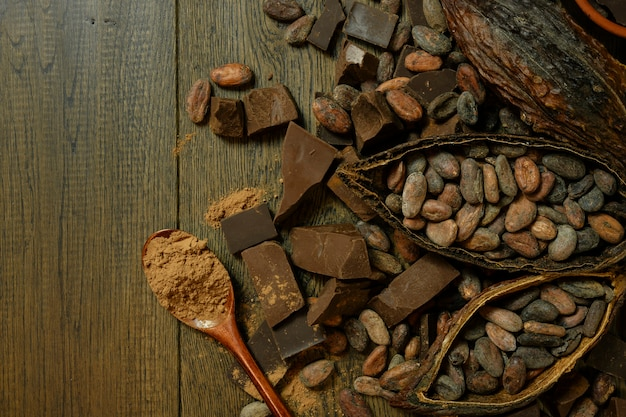 Открытый плод какао лежит на деревянном столе с какао-бобами