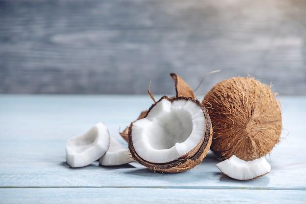 青い木製の背景に白脾髄でココナッツを開く