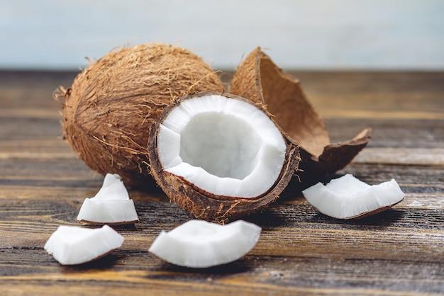 木製の背景に白脾髄でココナッツを開く