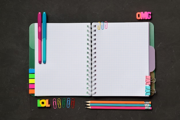 Open copy book with office and student supplies on black chalk