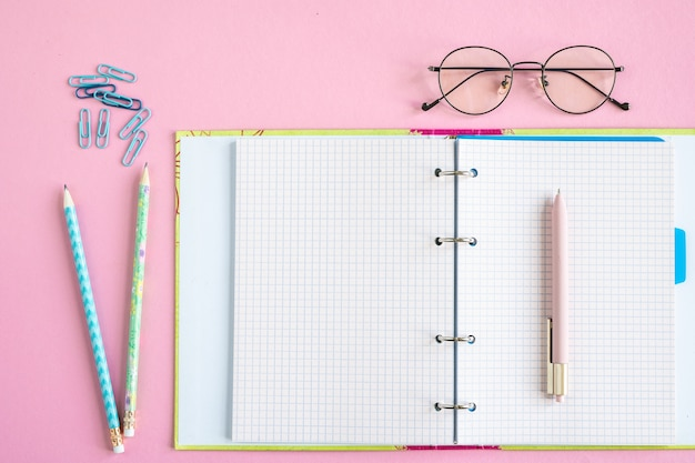 Откройте тетрадь или тетрадь с пустыми страницами, ручкой, двумя карандашами, зажимами и очками на розовом столе