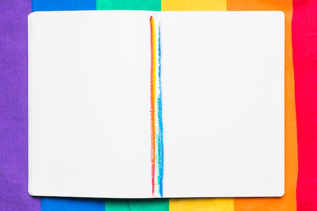 Open copybook with rainbow stripes