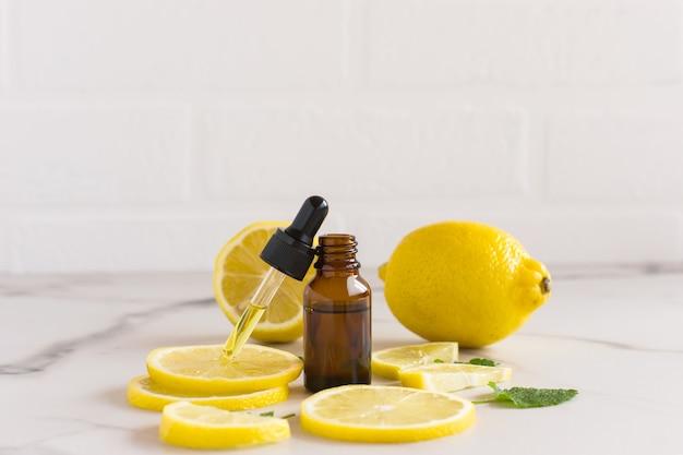 흰색 대리석 배경에 화장품 레몬 오일로 채워진 스포이드 스포이드가 있는 화장품 바이알을 엽니다. 레몬 조각, 멜리사 잎.