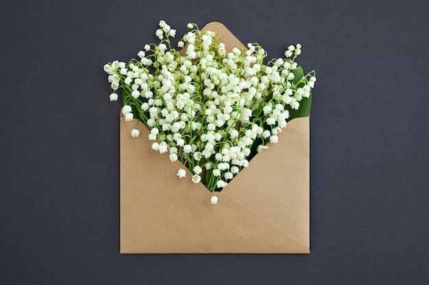밀접하게 회색 배경에 은방울꽃이 있는 열린 공예 봉투