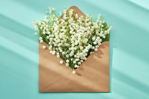 청록색 배경에 은방울꽃이 있는 열린 공예 봉투