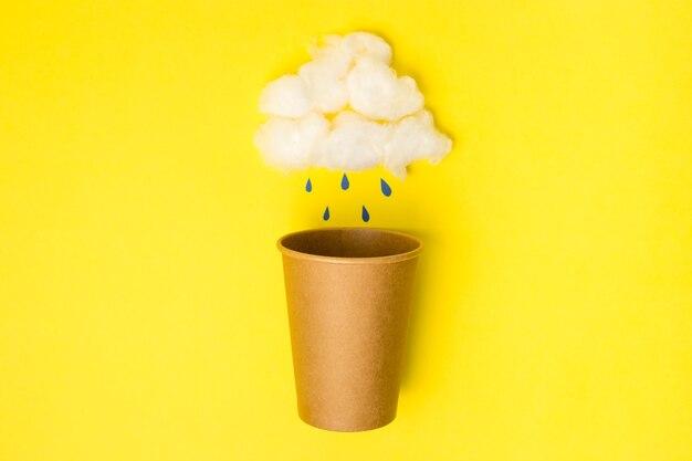 黄色の背景に脱脂綿の雲と紙のドロップでクラフト紙コップを開きます。フラットレイ。クリエイティブミニマルフードまたはウェザーコンセプト。コピースペース、ドリンクカップパッケージのモックアップ、雨の時間