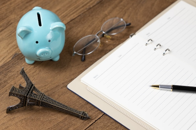 ペンエッフェル塔モデル貯金箱とメガネで木製のテーブルに日記の本を開く
