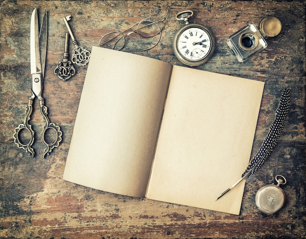 Open diary book and vintage writing tools on wooden table. feather pen, inkwell, keys. retro style toned picture with vignette