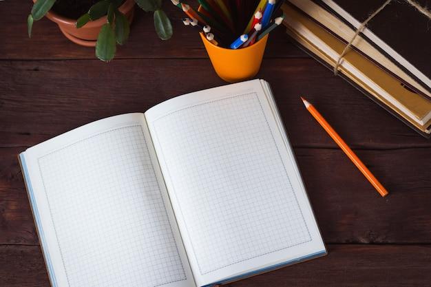 開いた日記、ガラスの色鉛筆、本の山、木の表面の部屋の花