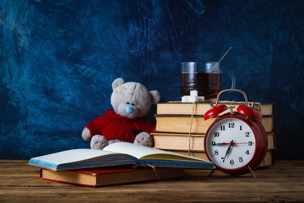 Open diary; cup of tea; books; toy bear; red alarm clock on blue surface. school concept