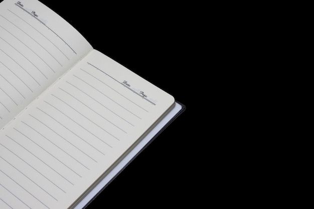 An open diary on isolated black background with copy space