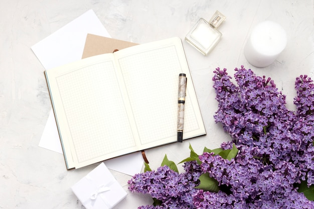 Open diary, pen, gift box, perfume bottle, candle, envelopes and a twig of lilac on a white stone surface. flat lay, top view