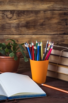 Open diary, a pile of books, colored pencils in a plastic glass, flower in a pot on a wooden background