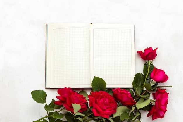 Open diary and red roses on a light stone background. flat lay, top view