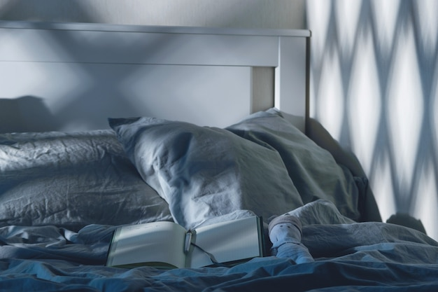 メンタルヘルスのための月明かりの夜の儀式で青い布でベッドに書くための日記を開く