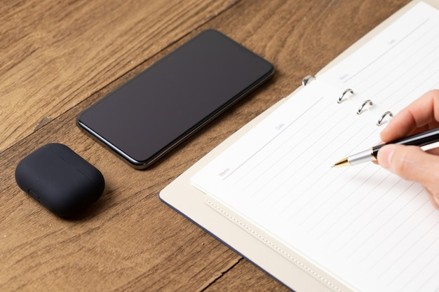 Open diary on wooden table with smart phone, head phone wireless and men hand writing on book