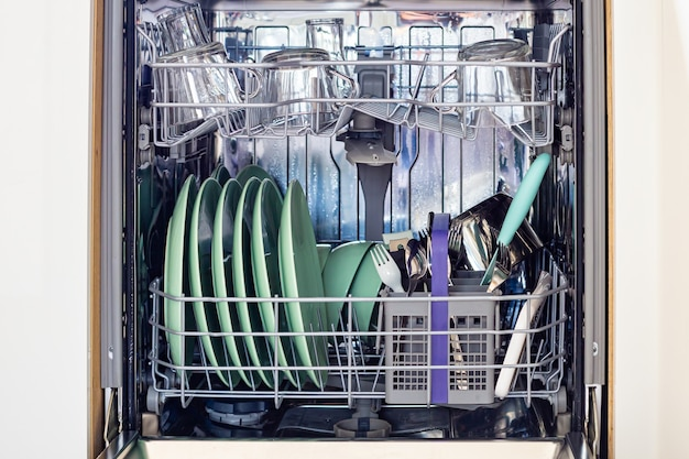 Open dishwasher with clean glasses and dishes
