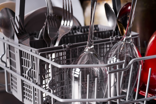Open dishwasher with clean wine glasses and utensils in it