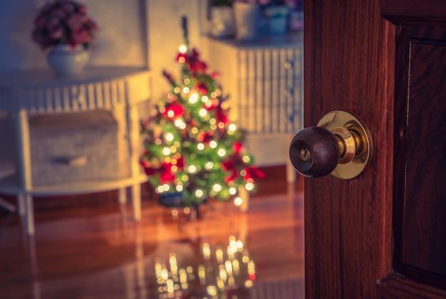 Откройте дверь и рождественская елка в комнате (фильтрованное изображение обрабатывается