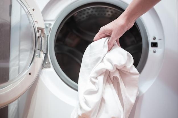 Открытая дверца стиральной машины с бельем